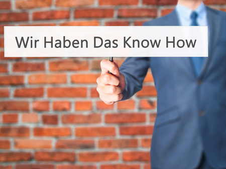 knowhow: Wir Haben Das Know How! (We Have the Know-How in German) - Businessman hand holding sign. Business, technology, internet concept. Stock Photo
