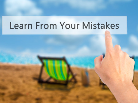 advise: Learn From Your Mistakes - Hand pressing a button on blurred background concept . Business, technology, internet concept. Stock Photo