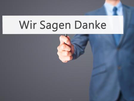 Wir Sagen Danke (We Say Thank You In German) - Businessman hand holding sign. Business, technology, internet concept. Stock Photo