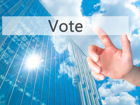 governing: Vote - Hand pressing a button on blurred background concept . Business, technology, internet concept. Stock Photo