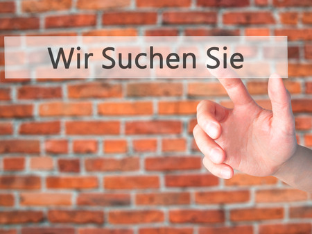 Wir Suchen Sie! (Looking For You in German) - Hand pressing a button on blurred background concept . Business, technology, internet concept. Stock Photo