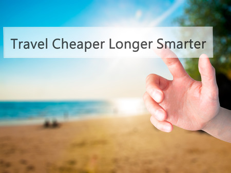 smarter: Travel Cheaper Longer Smarter - Hand pressing a button on blurred background concept . Business, technology, internet concept. Stock Photo