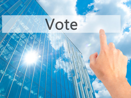 Vote - Hand pressing a button on blurred background concept . Business, technology, internet concept. Stock Photo