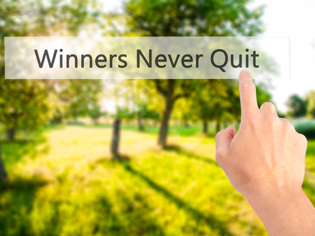 Winners Never Quit - Hand pressing a button on blurred background concept . Business, technology, internet concept. Stock Photo