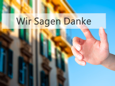 Wir Sagen Danke (We Say Thank You In German) - Hand pressing a button on blurred background concept . Business, technology, internet concept. Stock Photo
