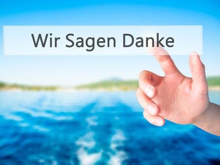comunicación escrita: Wir Sagen Danke (Nos dan las gracias en alemán) - Mano presionando un botón en concepto de fondo borroso. Negocios, la tecnología, el concepto de internet. Foto de stock