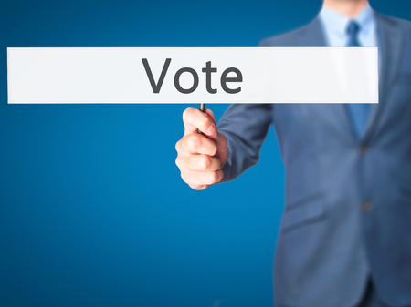 governing: Vote - Businessman hand holding sign. Business, technology, internet concept. Stock Photo Stock Photo