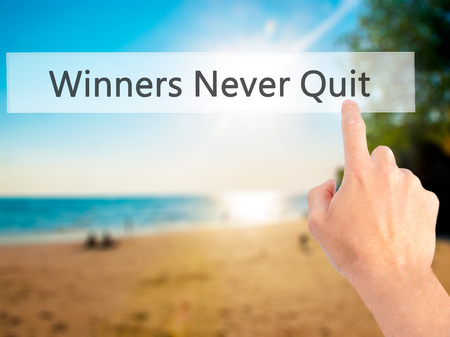 persevere: Winners Never Quit - Hand pressing a button on blurred background concept . Business, technology, internet concept. Stock Photo