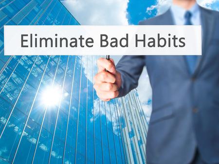 eliminating: Eliminate Bad Habits - Businessman hand holding sign. Business, technology, internet concept. Stock Photo Stock Photo