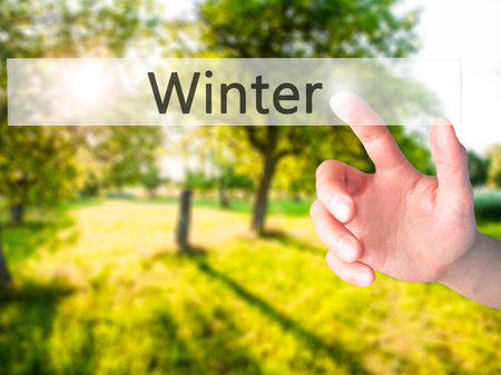Winter - Hand pressing a button on blurred background concept . Business, technology, internet concept. Stock Photo Stock Photo