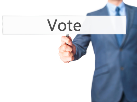 conscientious: Vote - Businessman hand holding sign. Business, technology, internet concept. Stock Photo Stock Photo