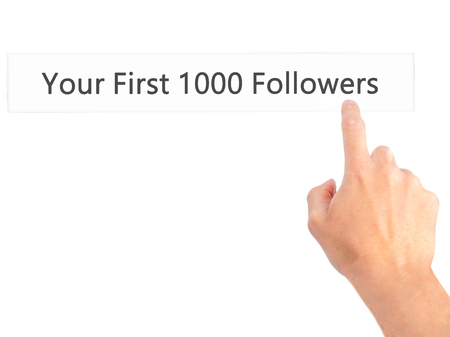 followers: Your First 1000 Followers - Hand pressing a button on blurred background concept . Business, technology, internet concept. Stock Photo Stock Photo