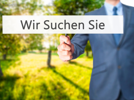 Wir Suchen Sie! (Looking For You in German) - Businessman hand holding sign. Business, technology, internet concept. Stock Photo