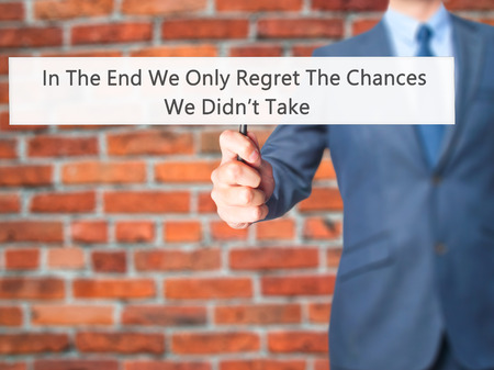 In The End We Only Regret The Chances We Didnt Take - Businessman hand holding sign. Business, technology, internet concept. Stock Photo Stock Photo
