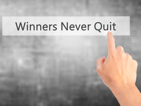 persist: Winners Never Quit - Hand pressing a button on blurred background concept . Business, technology, internet concept. Stock Photo