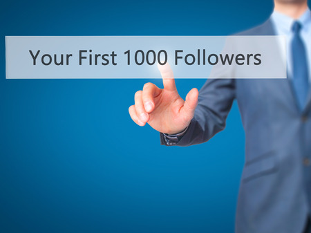 followers: Your First 1000 Followers - Businessman hand touch  button on virtual  screen interface. Business, technology concept. Stock Photo