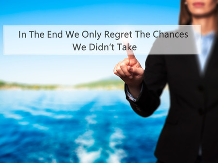 regret: In The End We Only Regret The Chances We Didnt Take - Businesswoman pressing high tech  modern button on a virtual background. Business, technology, internet concept. Stock Photo Stock Photo