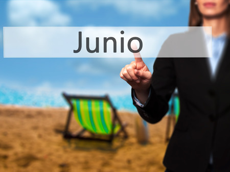 Junio (June in Spanish) - Businesswoman pressing high tech  modern button on a virtual background. Business, technology, internet concept. Stock Photo Stock Photo