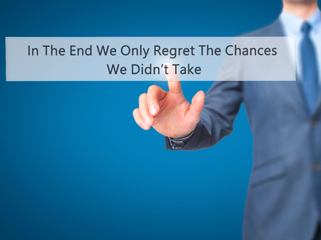 remorse: In The End We Only Regret The Chances We Didnt Take - Businessman hand touch  button on virtual  screen interface. Business, technology concept. Stock Photo