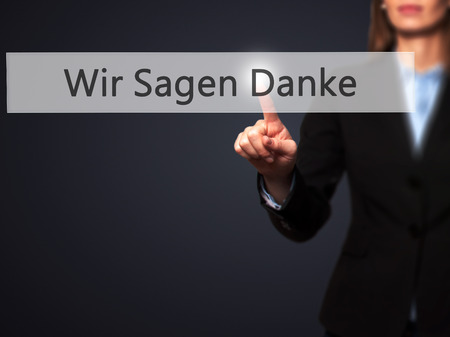 acknowledgment: Wir Sagen Danke (We Say Thank You In German) - Businesswoman pressing high tech  modern button on a virtual background. Business, technology, internet concept. Stock Photo