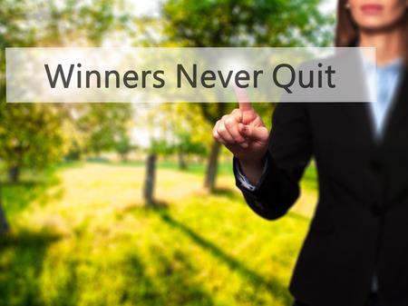 Winners Never Quit - Businesswoman pressing high tech  modern button on a virtual background. Business, technology, internet concept. Stock Photo