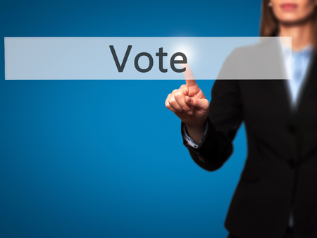 governing: Vote - Businesswoman pressing high tech  modern button on a virtual background. Business, technology, internet concept. Stock Photo Stock Photo