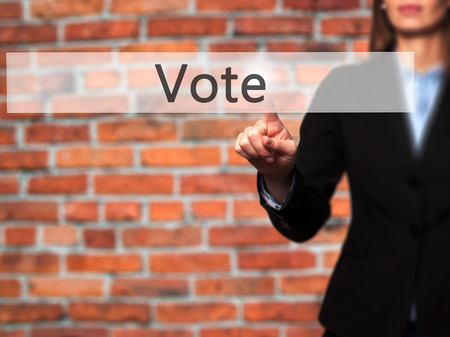 conscientious: Vote - Businesswoman pressing high tech  modern button on a virtual background. Business, technology, internet concept. Stock Photo Stock Photo