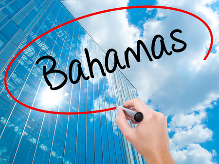 Man Hand writing Bahamas with black marker on visual screen. Business, technology, internet concept. Modern business skyscrapers background. Stock Photo