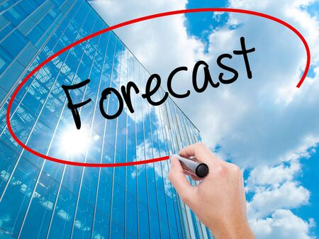 Man Hand writing Forecast with black marker on visual screen. Business, technology, internet concept. Modern business skyscrapers background. Stock Photo