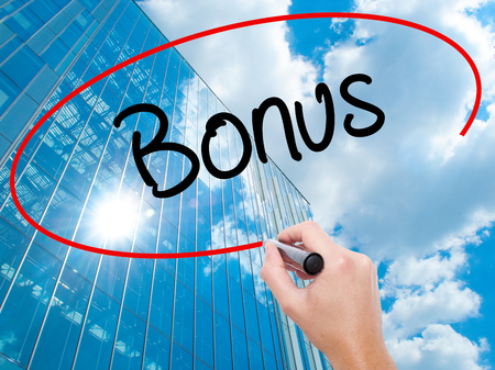 Man Hand writing Bonus with black marker on visual screen.  Business, technology, internet concept. Modern business skyscrapers background. Stock Photo