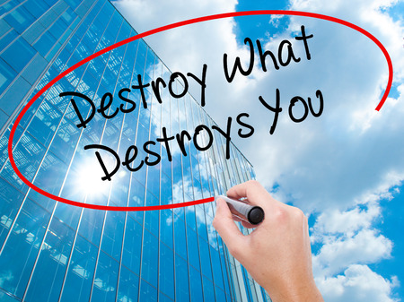 Man Hand writing Destroy What Destroys You with black marker on visual screen.  Business, technology, internet concept. Modern business skyscrapers background. Stock Photo