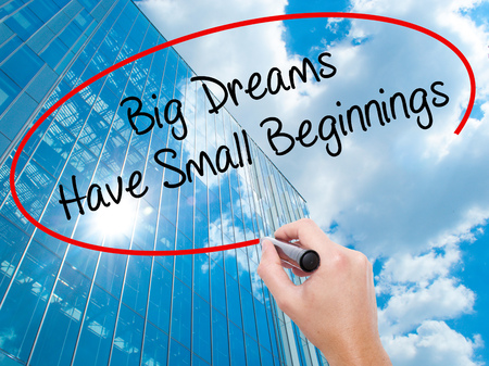 Man Hand writing Big Dreams Have Small Beginnings with black marker on visual screen. Business, technology, internet concept. Modern business skyscrapers background. Stock Photo
