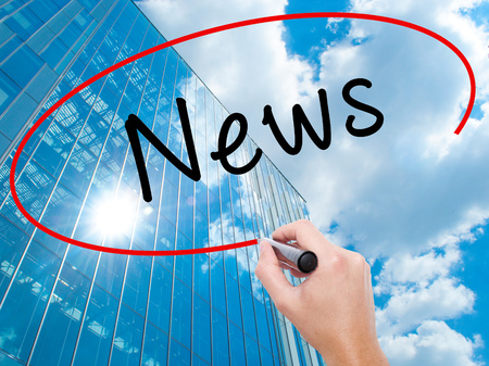 actuality: Man Hand writing News with black marker on visual screen. Business, technology, internet concept. Modern business skyscrapers background. Stock Image
