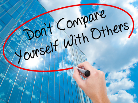 Man Hand writing Dont Compare Yourself With Others with black marker on visual screen.  Business, technology, internet concept. Modern business skyscrapers background. Stock Photo