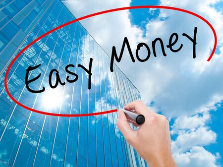 guidepost: Man Hand writing Easy Money with black marker on visual screen. Business, technology, internet concept. Modern business skyscrapers background. Stock Image