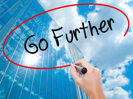 Man Hand writing Go Further with black marker on visual screen. Business, technology, internet concept. Modern business skyscrapers background. Stock Photo