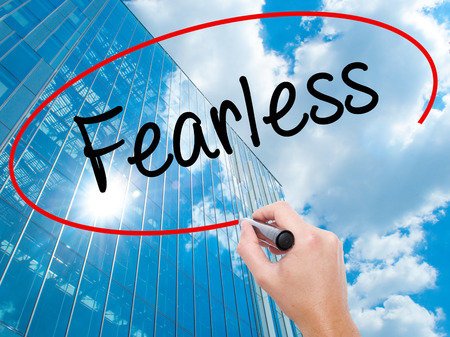 Man Hand writing Fearless  with black marker on visual screen.  Business, technology, internet concept. Modern business skyscrapers background. Stock Photo