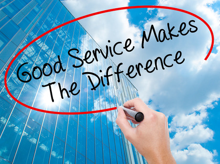 Man Hand writing Good Service Makes The Difference with black marker on visual screen. Business, technology, internet concept. Modern business skyscrapers background. Stock Photo