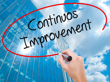 Man Hand writing Continuos Improvement with black marker on visual screen. Business, technology, internet concept. Modern business skyscrapers background. Stock Photo