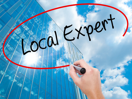 Man Hand writing  Local Expert with black marker on visual screen.  Business, technology, internet concept. Modern business skyscrapers background. Stock Photo