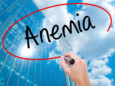 decreased: Man Hand writing Anemia  with black marker on visual screen.  Business, technology, internet concept. Modern business skyscrapers background. Stock Photo