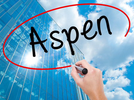 Man Hand writing Aspen with black marker on visual screen. Business, technology, internet concept. Modern business skyscrapers background. Stock Photo