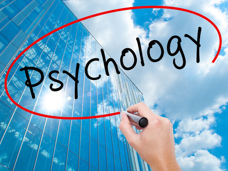 antisocial: Man Hand writing Psychology with black marker on visual screen. Business, technology, internet concept. Modern business skyscrapers background. Stock Image Stock Photo