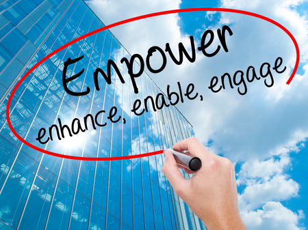 Man Hand writing Empower enhance, enable, engage with black marker on visual screen. Business, technology, internet concept. Modern business skyscrapers background. Stock Photo Stock Photo