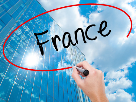 the loire: Man Hand writing France with black marker on visual screen. Business, technology, internet concept. Modern business skyscrapers background. Stock Photo Stock Photo