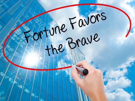 Hombre de la mano escribiendo Fortune Favors the Brave con marcador negro en la pantalla visual. Negocios, tecnología, concepto de internet. Fondo de rascacielos de negocios modernos. Foto de stock