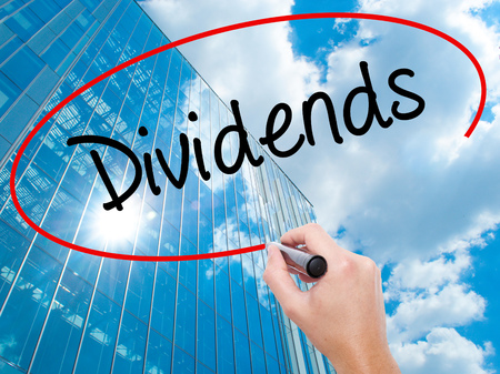 Man Hand writing Dividends with black marker on visual screen.  Business, technology, internet concept. Modern business skyscrapers background. Stock Photo