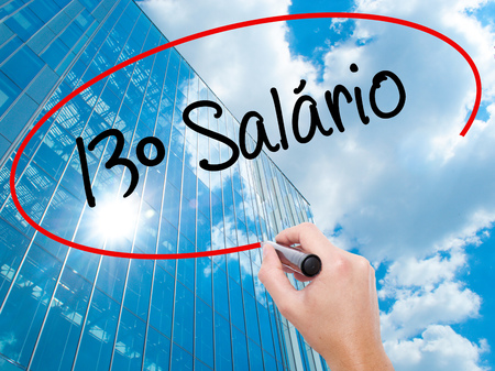 Man Hand writing 13 Salary (13o salario In Portuguese)  with black marker on visual screen.  Business, technology, internet concept. Modern business skyscrapers background. Stock Photo