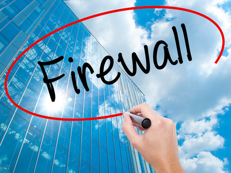 Man Hand writing Firewall  with black marker on visual screen.  Business, technology, internet concept. Modern business skyscrapers background. Stock Photo Stock Photo