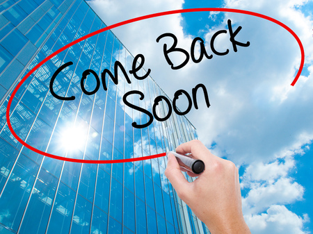 will return: Man Hand writing Come Back Soon with black marker on visual screen.  Business, technology, internet concept. Modern business skyscrapers background. Stock Photo